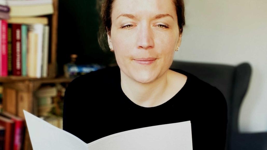 Svenja Hirsch sitzt vorgelehnt auf einem Hocker und liest in ein paar ausgedruckten Seiten