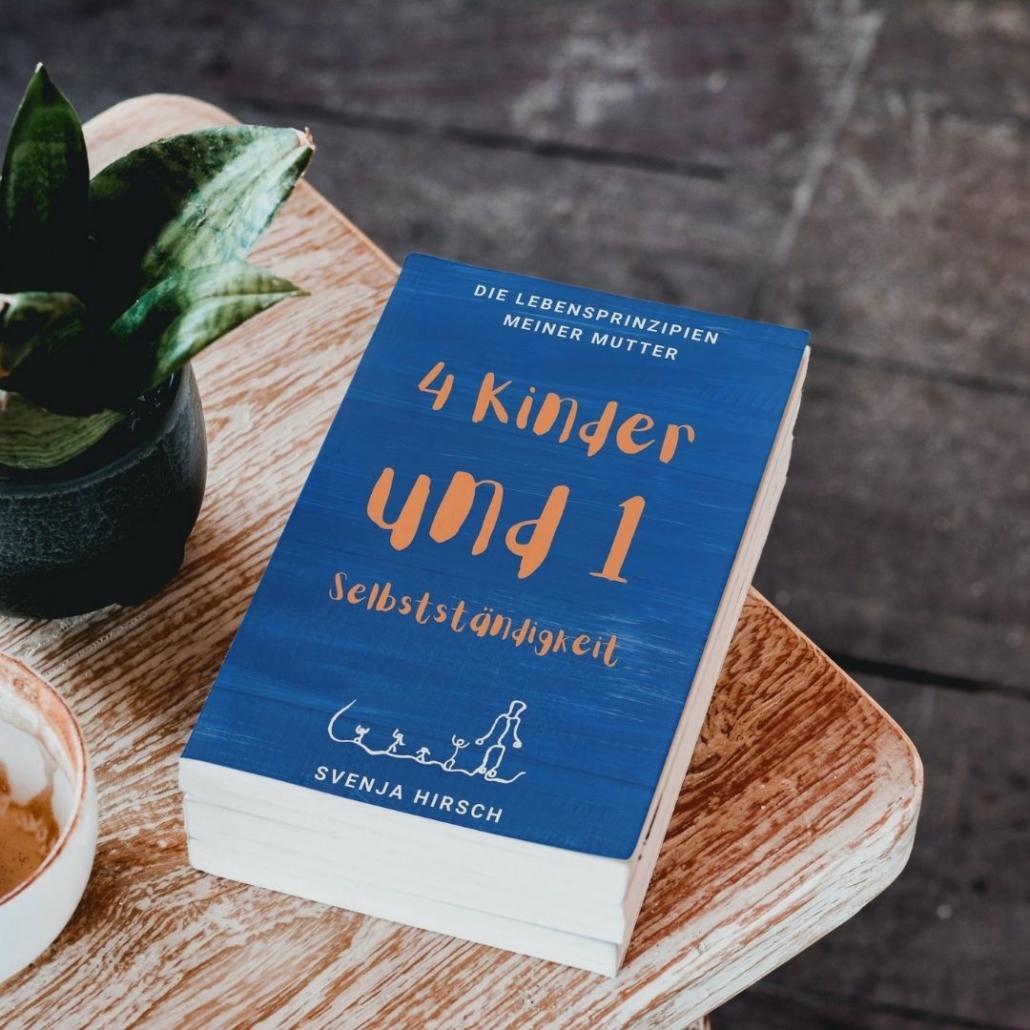 Vier Kinder und eine Selbstständigkeit Buch liegt auf Tische neben Pflanze und Kaffee