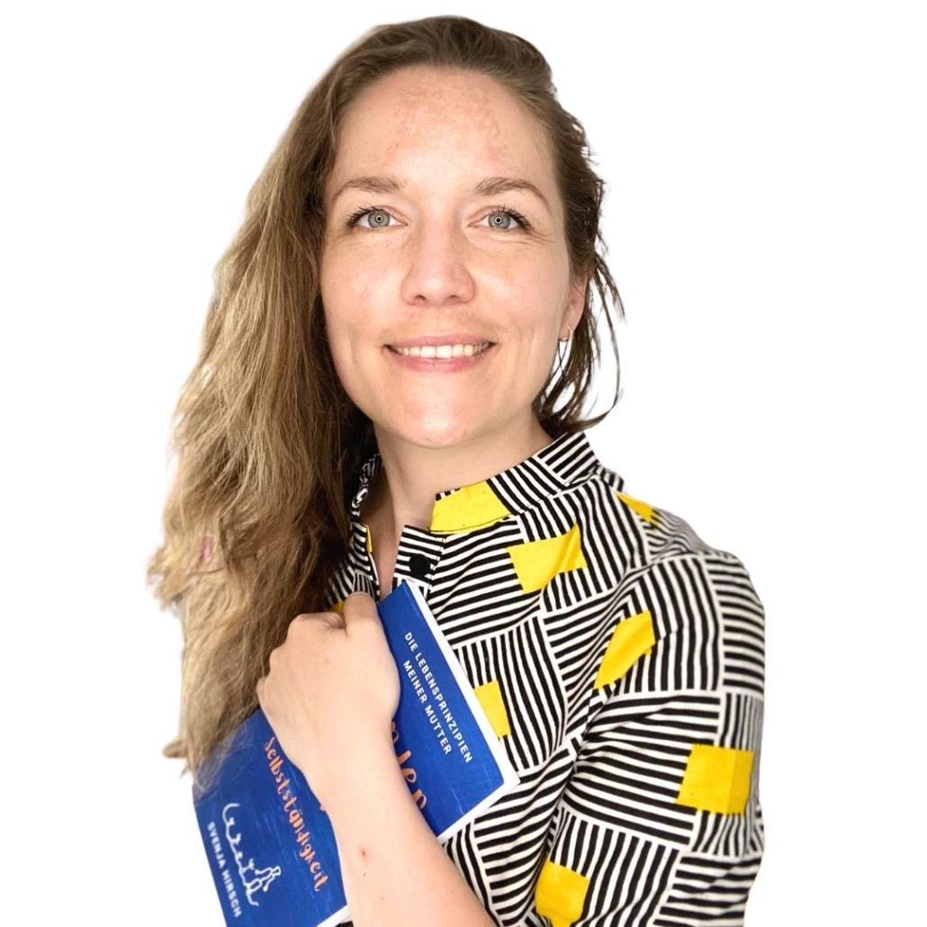 Svenja Hirsch in gemustertem Kleid und Buch in der Hand, freigestellt