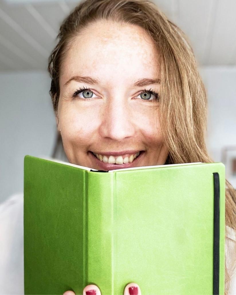 Svenja Hirsch mit einem grünen Buch in der Hand, weißer Hintergrund. Buchcoach, Buchcoachin, Co-Autorin, Selfpublishing